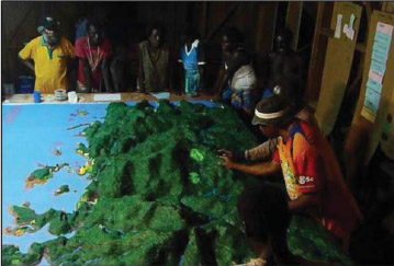 PHOTO: Boeboe community members add markers for local and traditonal ecological knowledge to the relief model of their village. Photo from J. X. Leon et al.(http://dx.doi.org/10.1080/08920753.2015.1046808)